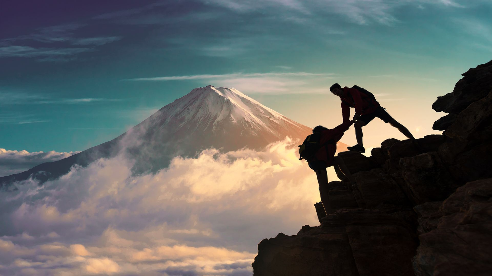 Young asian couple hikers climbing up on the peak of mountain near mountain fuji .Climbing ,Helps and Team work concept